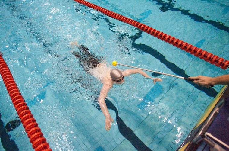 Visually impaired swimmer being tapped to turn