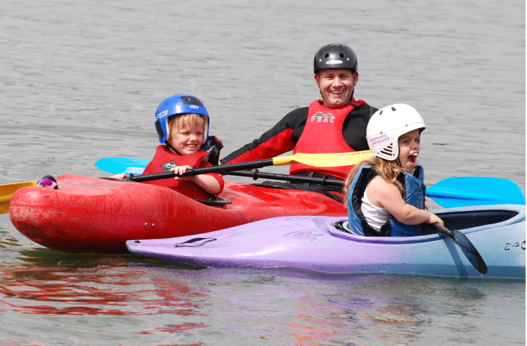 Two people with dwarfism canoeing with instructor