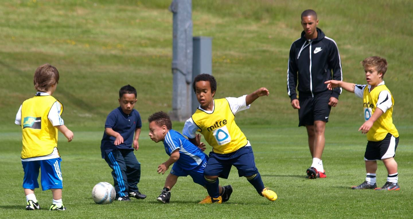 Group of boys with dwarfism playing football