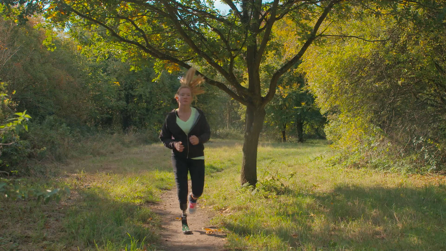 Cassie running in a park with her running blade on