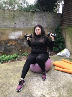 Jess exercising with weights and an exercise ball