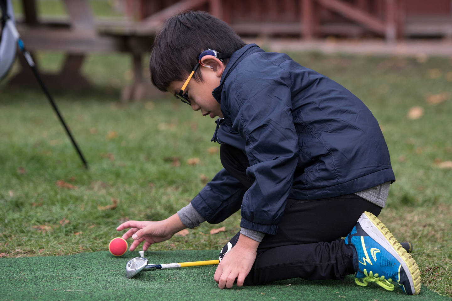 Young boy with hearing impairment putting golf ball on tee.
