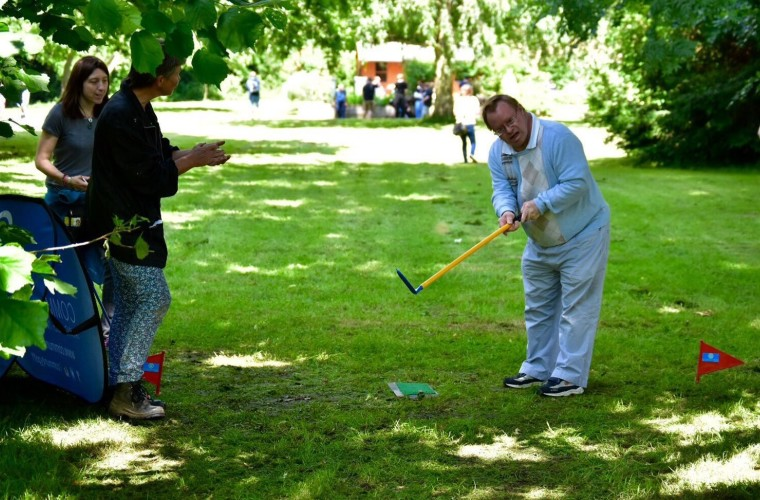 Man with a learning disability playing golf shot in tournament