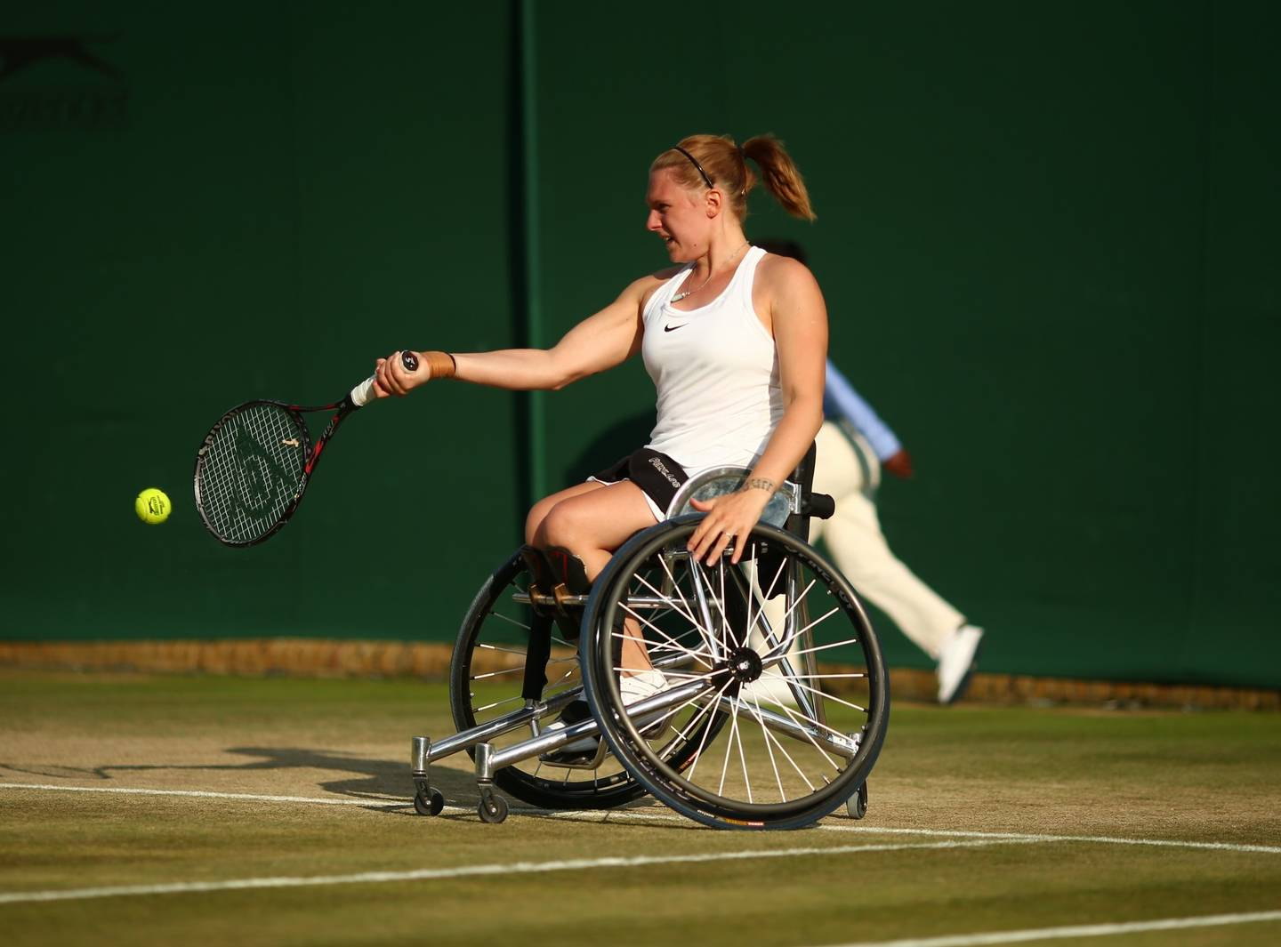 Jordanne Whiley, wheelchair tennis player hitting forehand on grass court