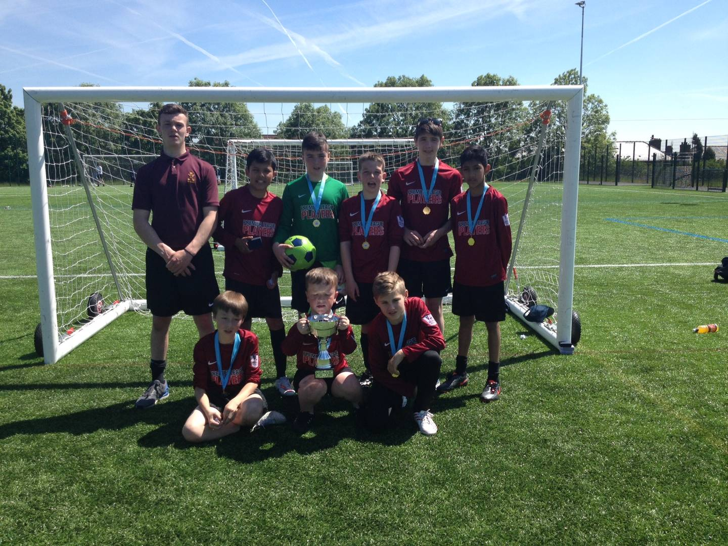 Asa and his football team on the pitch with their league trophy