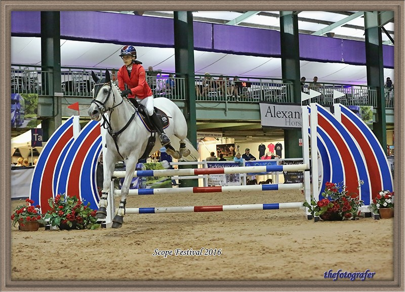 Evie riding her horse at a showjumping event