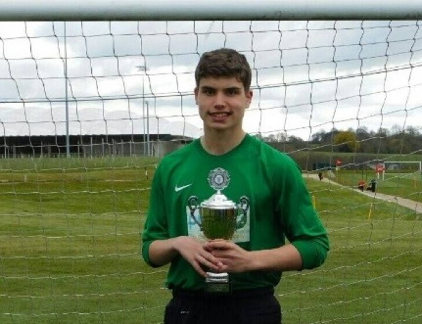 Ben Meadows in front of the net with a trophy