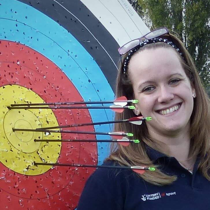 Lauren Sanders standing next to archery target