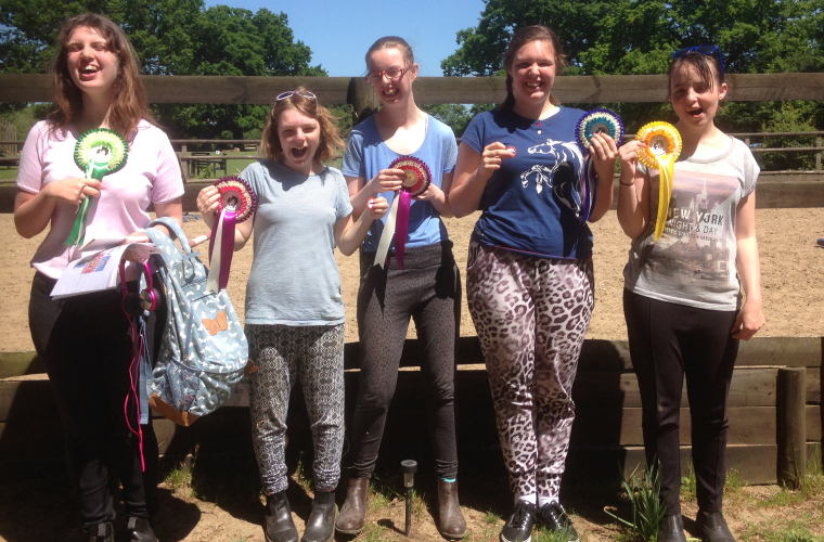 Riding students celebrating with their rosettes