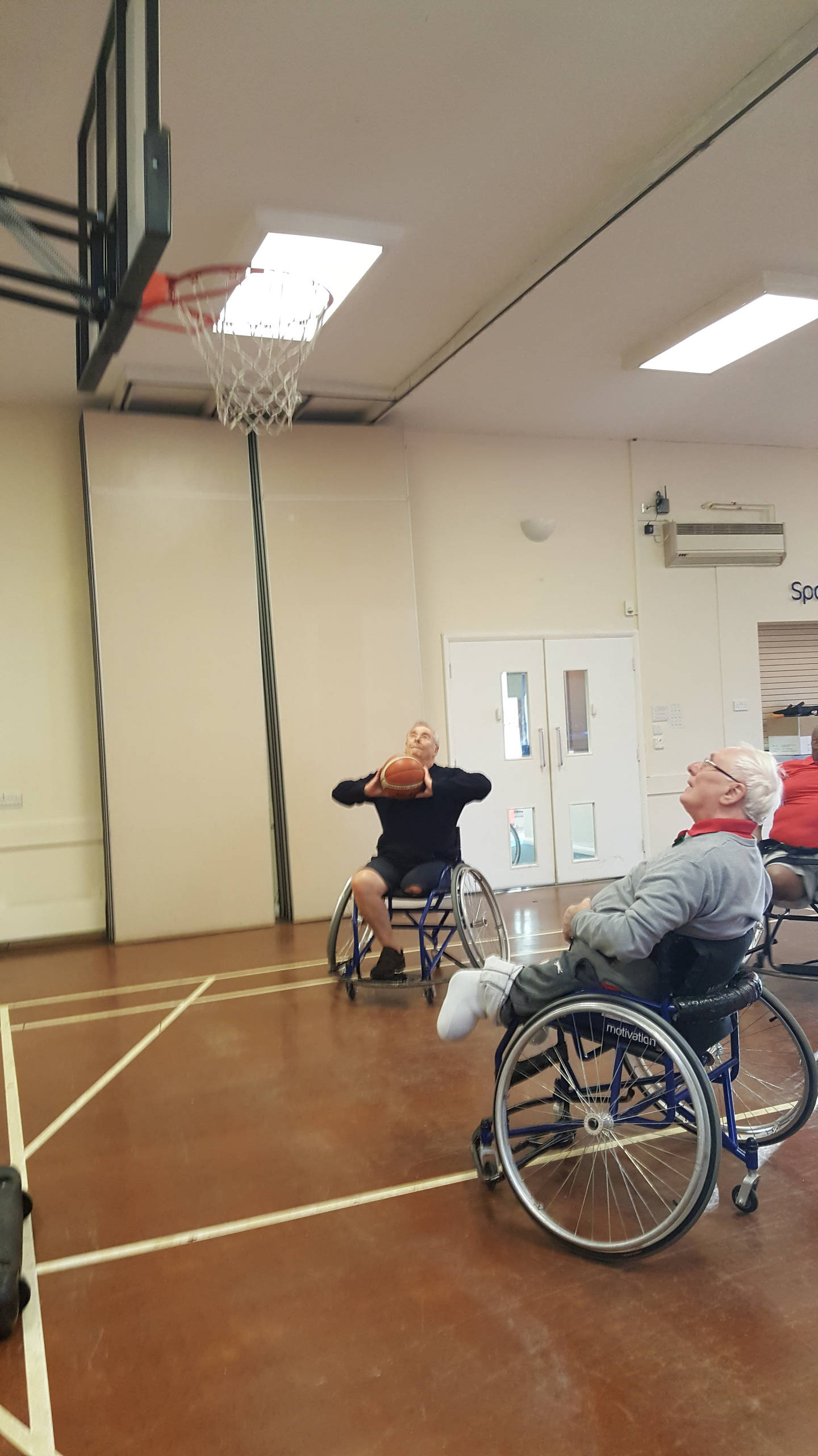 Two people playing wheelchair basketball.