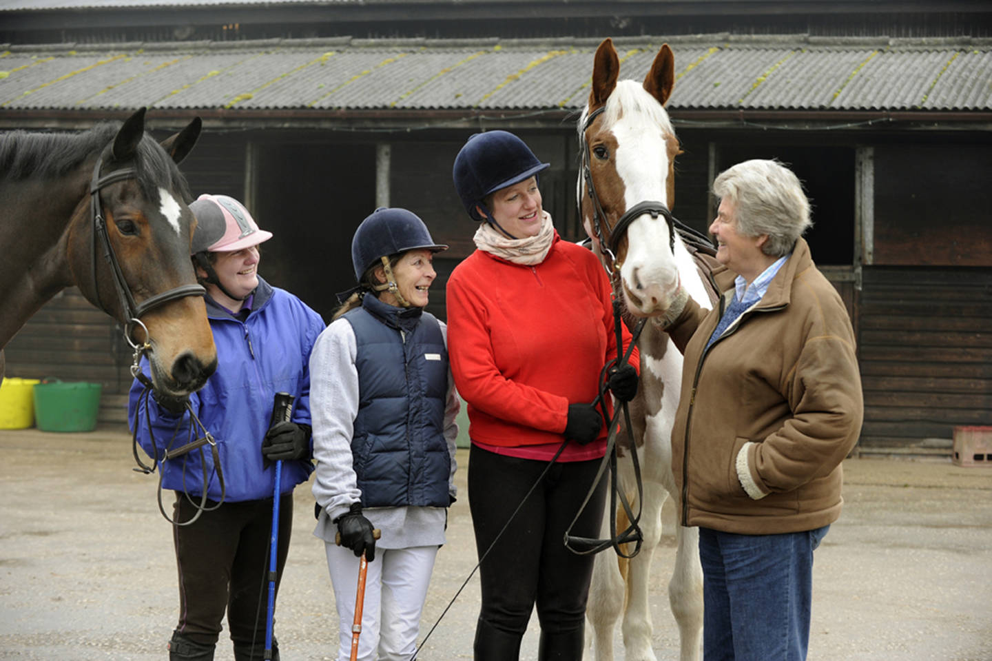Group of disabled riders in paddock with two horses