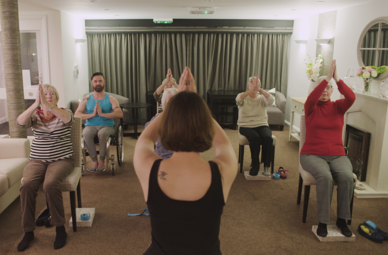 Presenter Kris taking part in a seated yoga session for older people