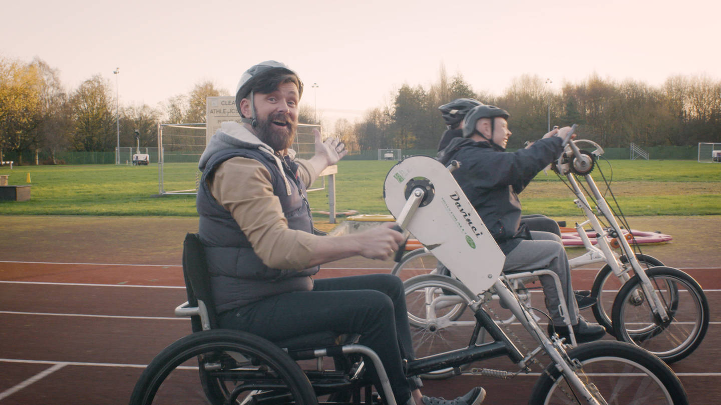 Presenter Kris and friends cycling on athletics track using an adapted bikes