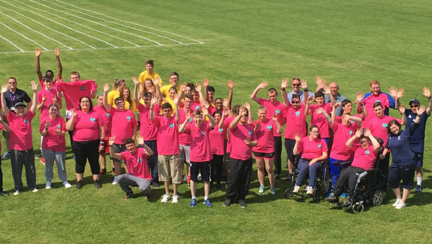 Group photo of disabled and non disabled students, teachers and staff on playing field.