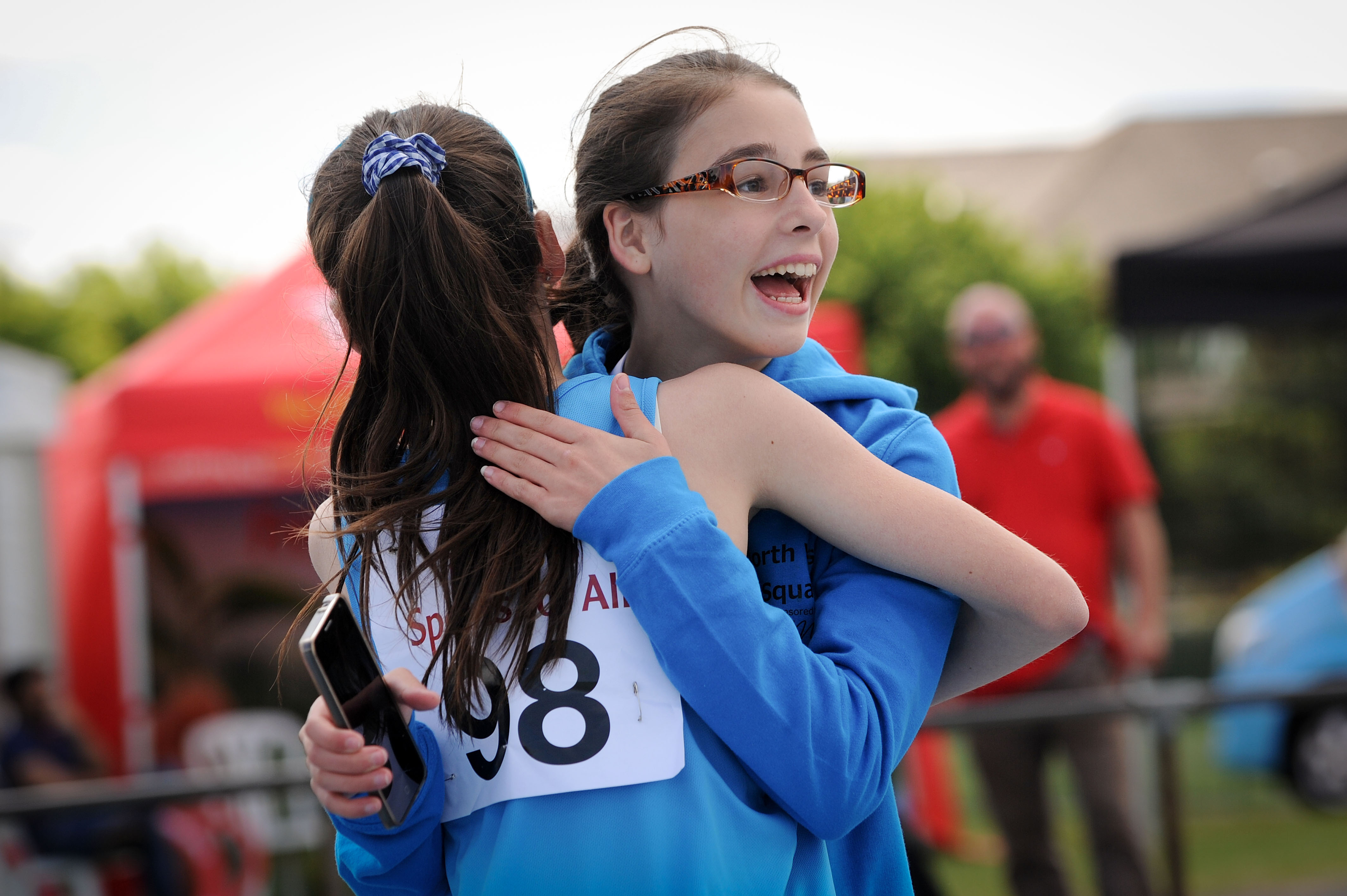 Two girl athletes hug after a race