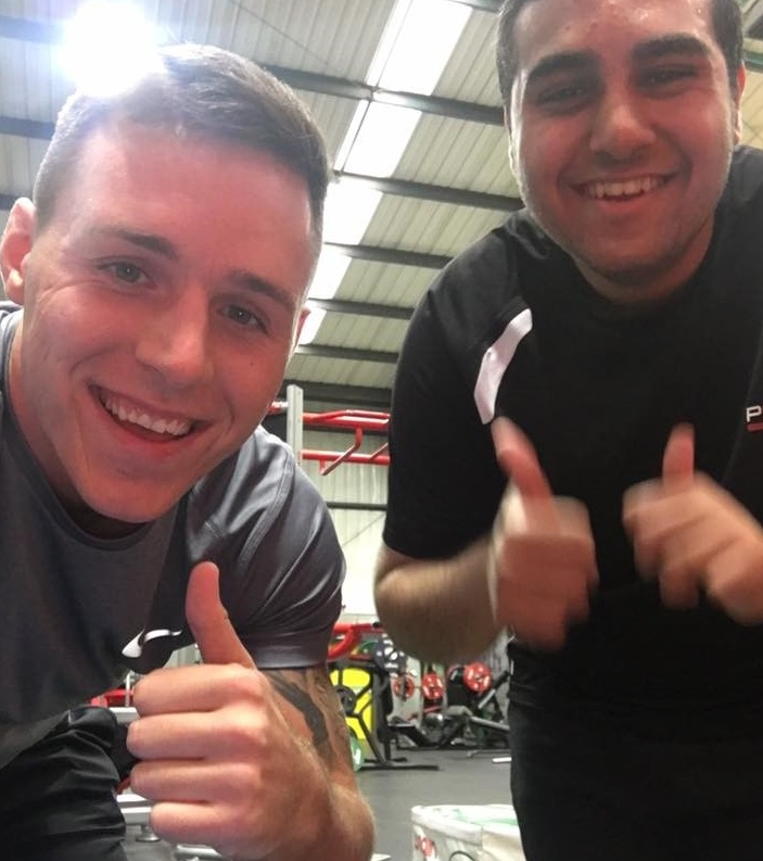 Sami with Ben in the gym, thumbs up to camera