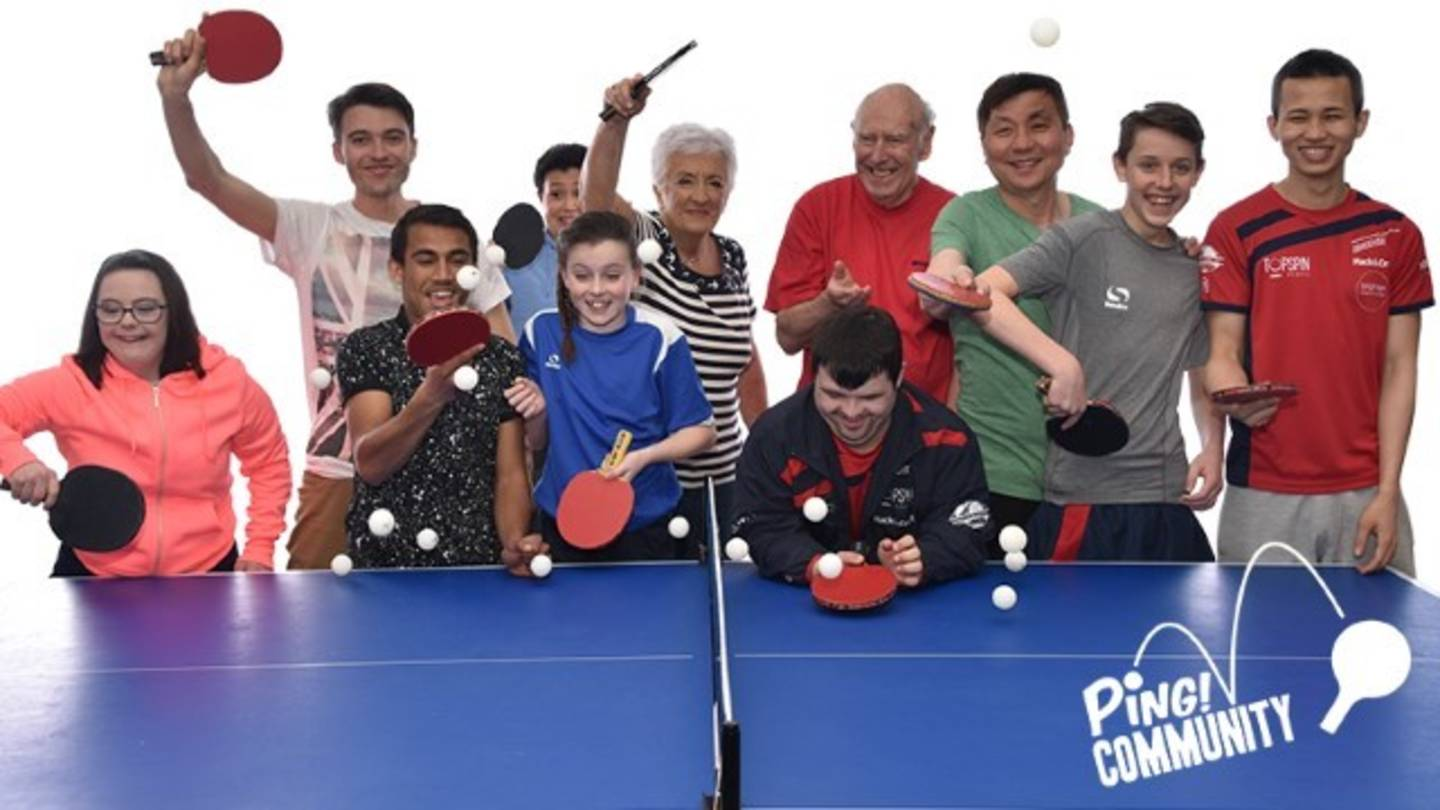 People of different ages and backgrounds smiling ready to play table tennis