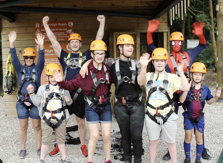 Children in climbing gear waving to camera.