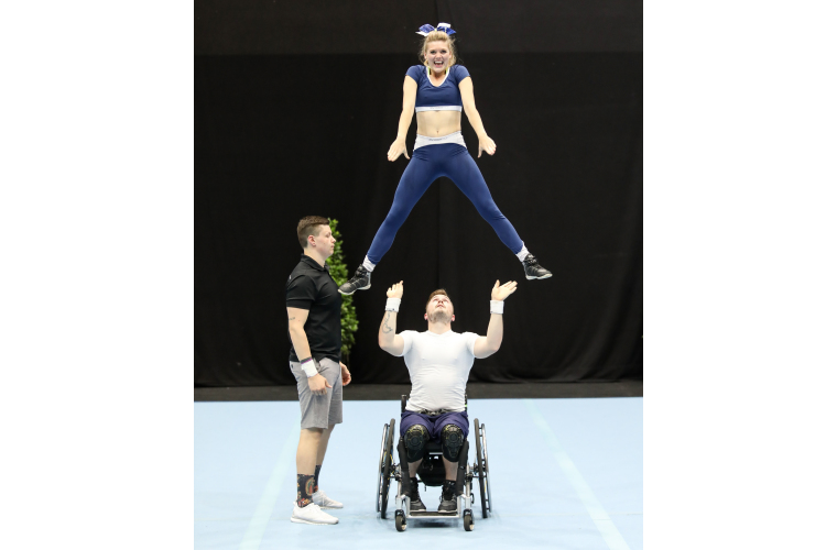 Rick lifting Chantal at a para-cheer competition.