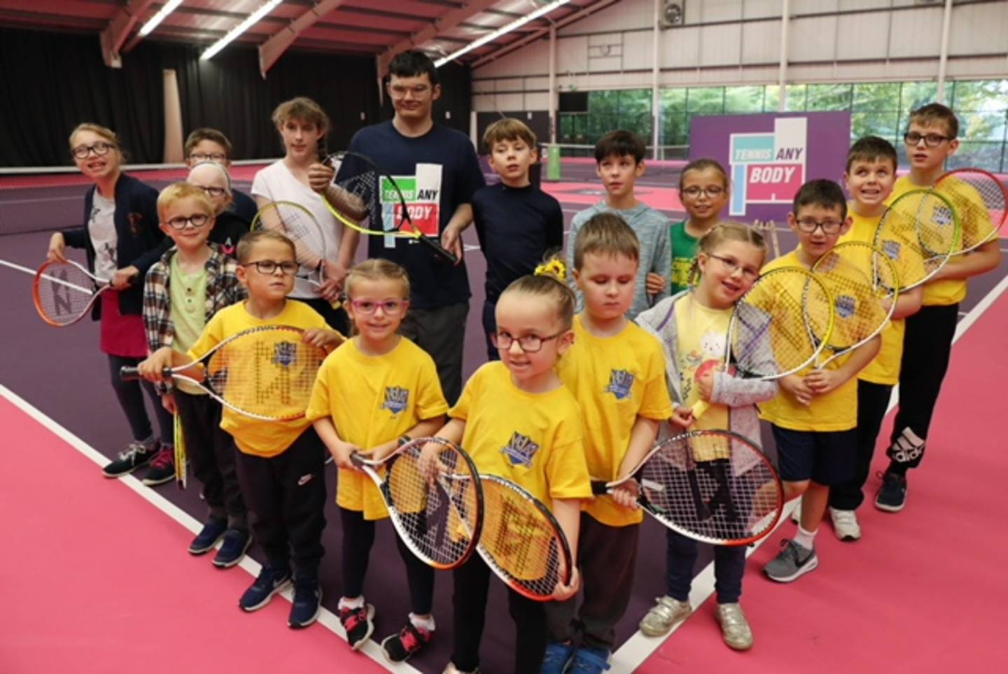 Group of children and tennis coach with tennis rackets in hand smiling to camera.