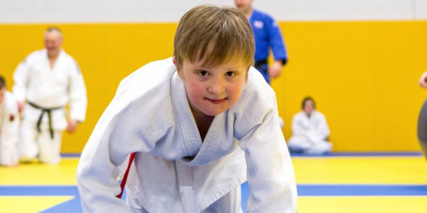 Young boy on smiling to camera in judo gear.