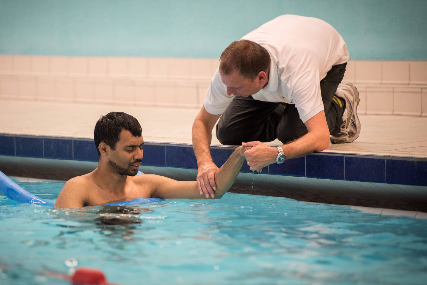 Swimming teacher supporting visually impaired man in swimming pool