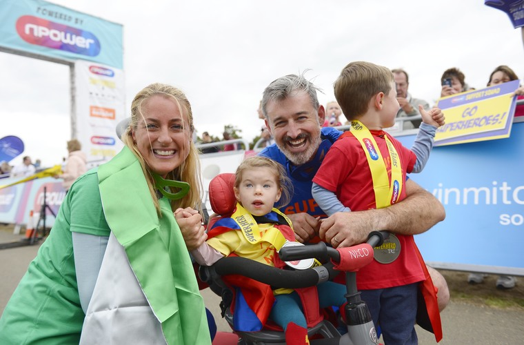 Family holding medals after finishing Superhero tri event