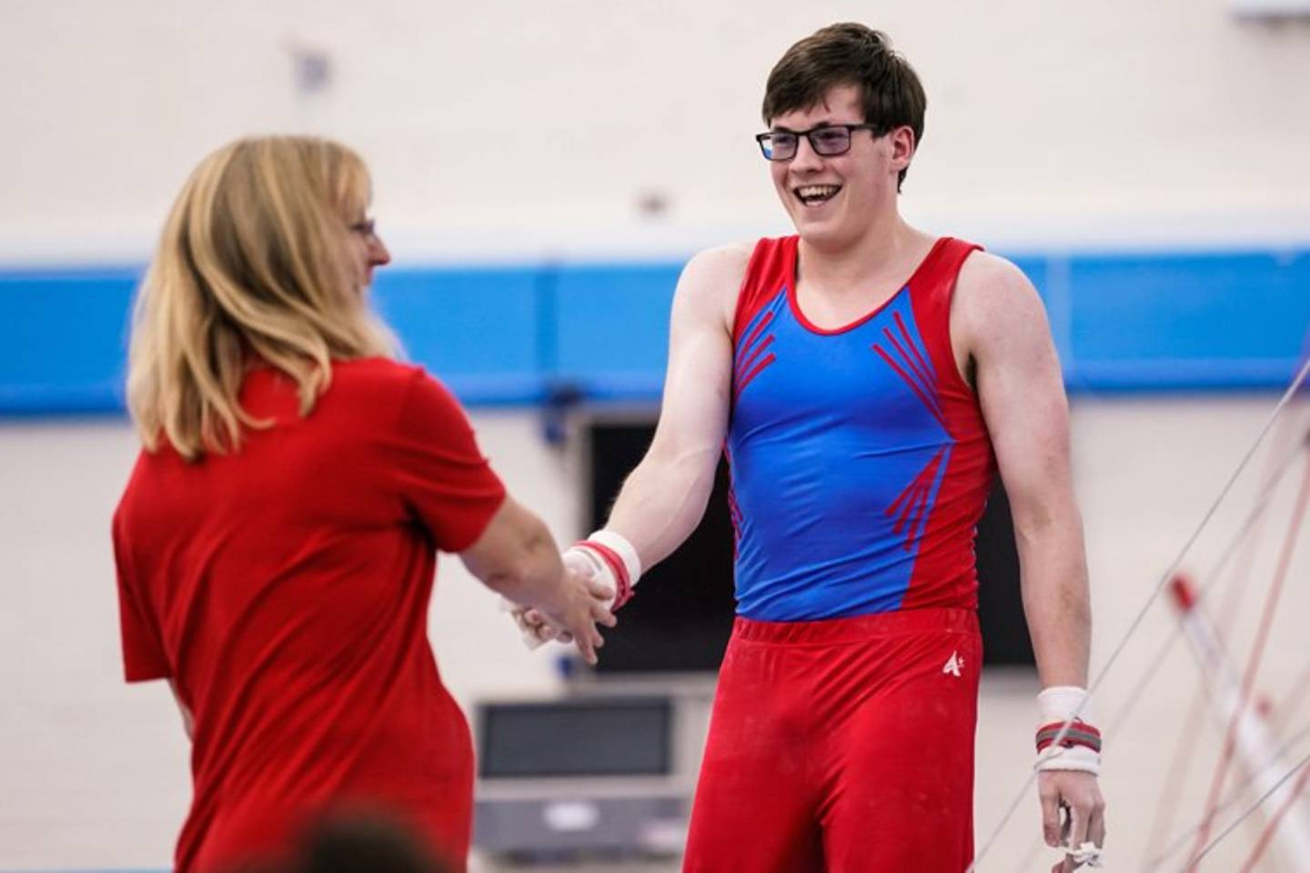 Male disabled gymnast smiling and giving his coach a high five
