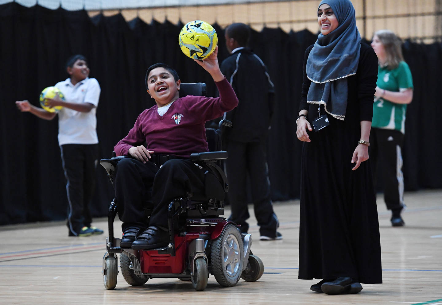 Boy in powerchair with football in hand laughing with girl stood next to him smiling.