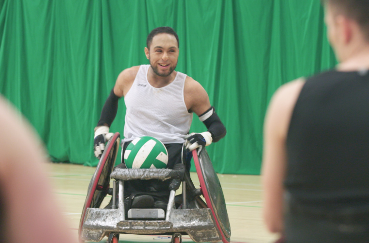 Wheelchair rugby player with ball smiling on court