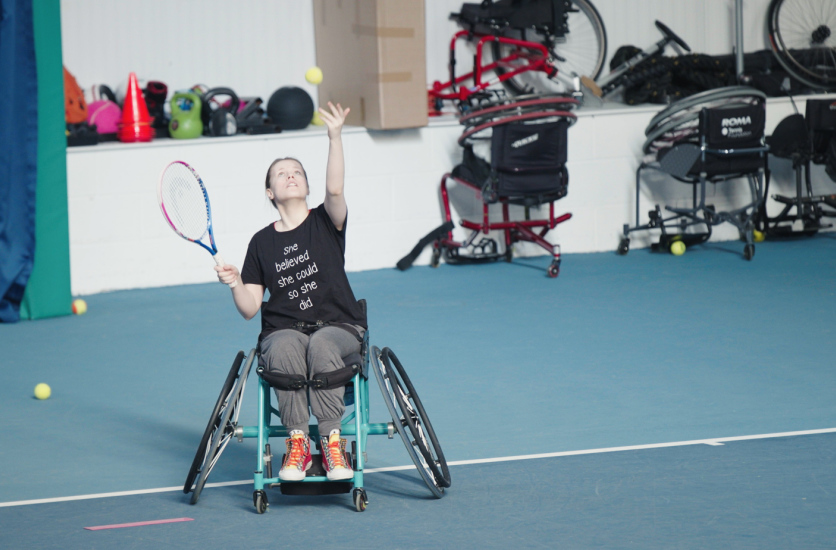Wheelchair tennis player serving in game