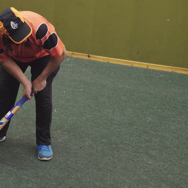 Visually impaired batter and wicket keeper waiting for cricket ball delivery