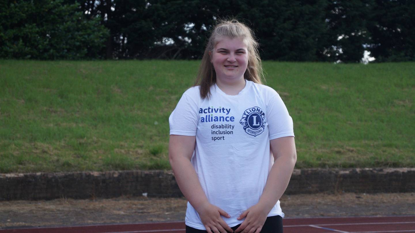 Ellie wearing Activity Alliance t-shirt on running track.