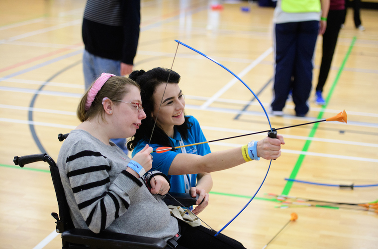 Young woman in a wheelchair taking part in archery with supporter