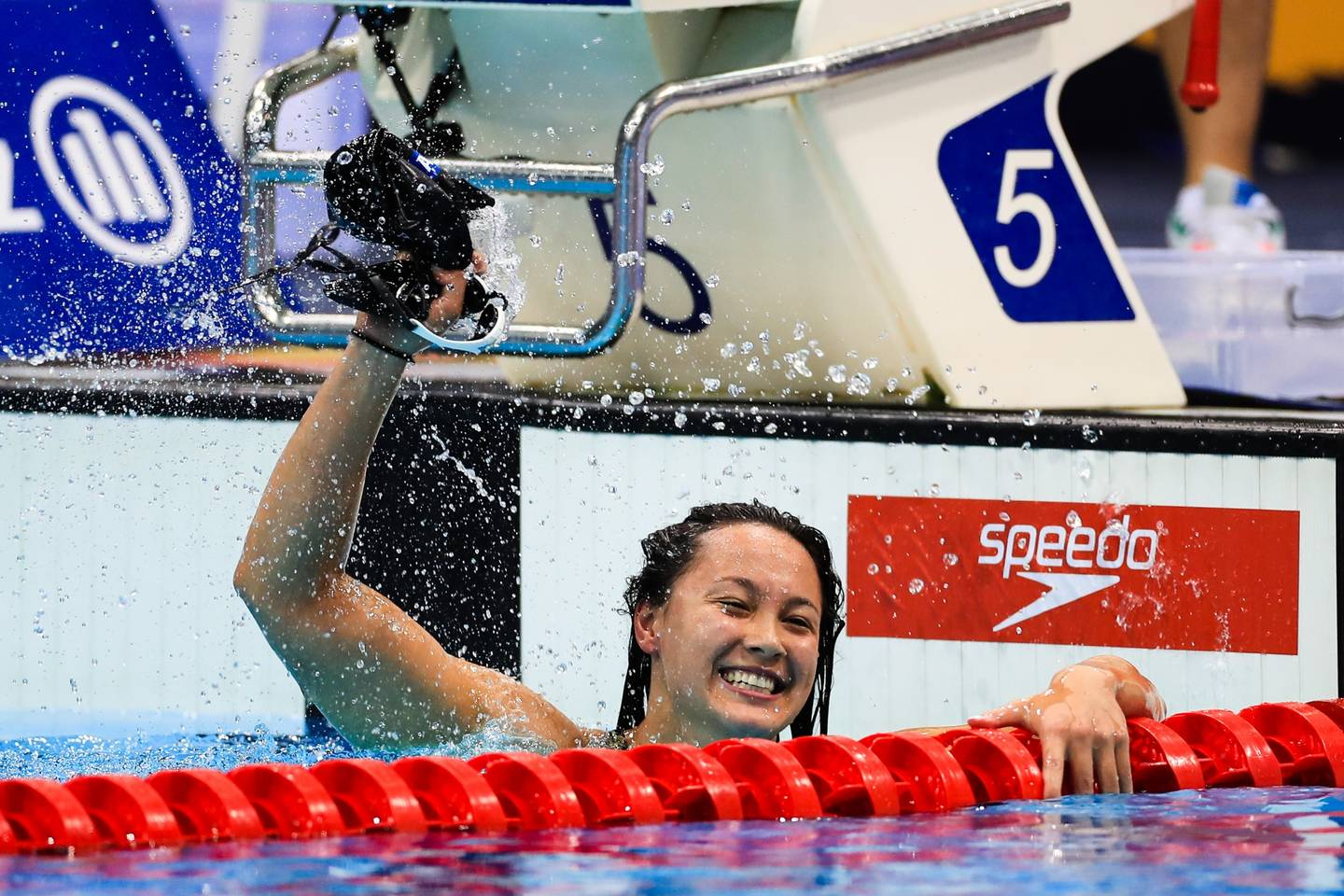 Alice Tai celebrating after winning race in swimming pool