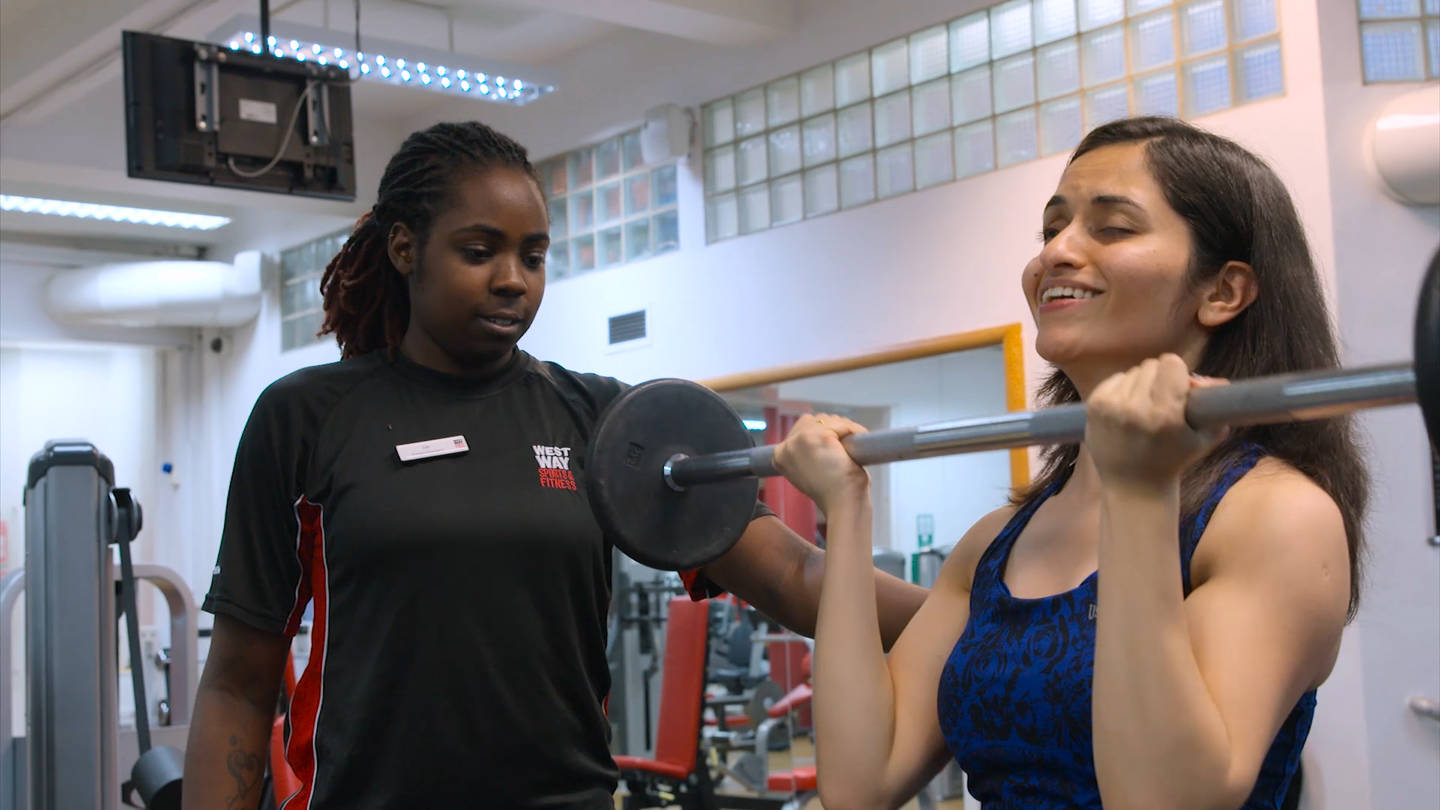 Visually impaired woman working out in gym with support of her gym instructor.