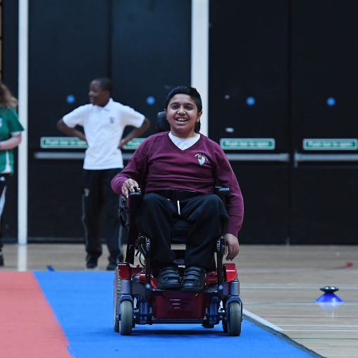 Boy in a powerchair having fun at school sports event