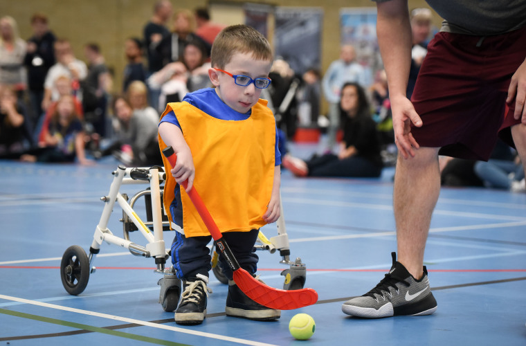 ung boy with dwarfism taking part in an indoor hockey game