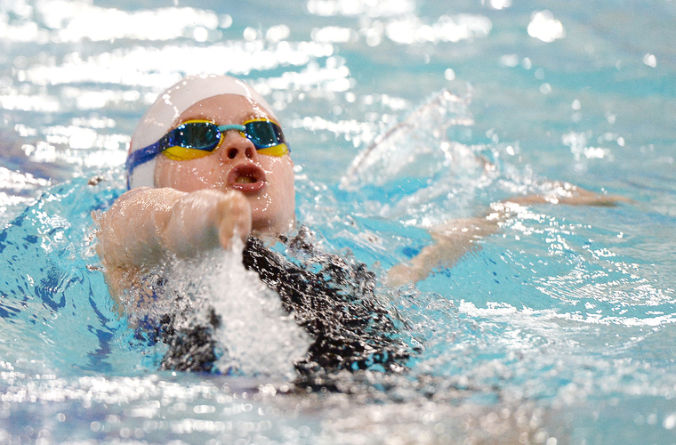Young swimmer with upper limb impairment swimming backstroke in pool
