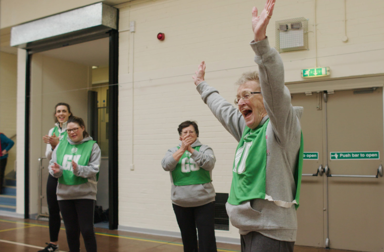 Older woman celebrates scoring a goal in game of netball