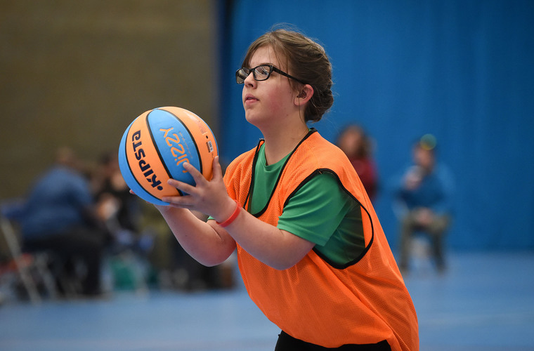 Young woman with dwarfism and hearing impairment playing basketball