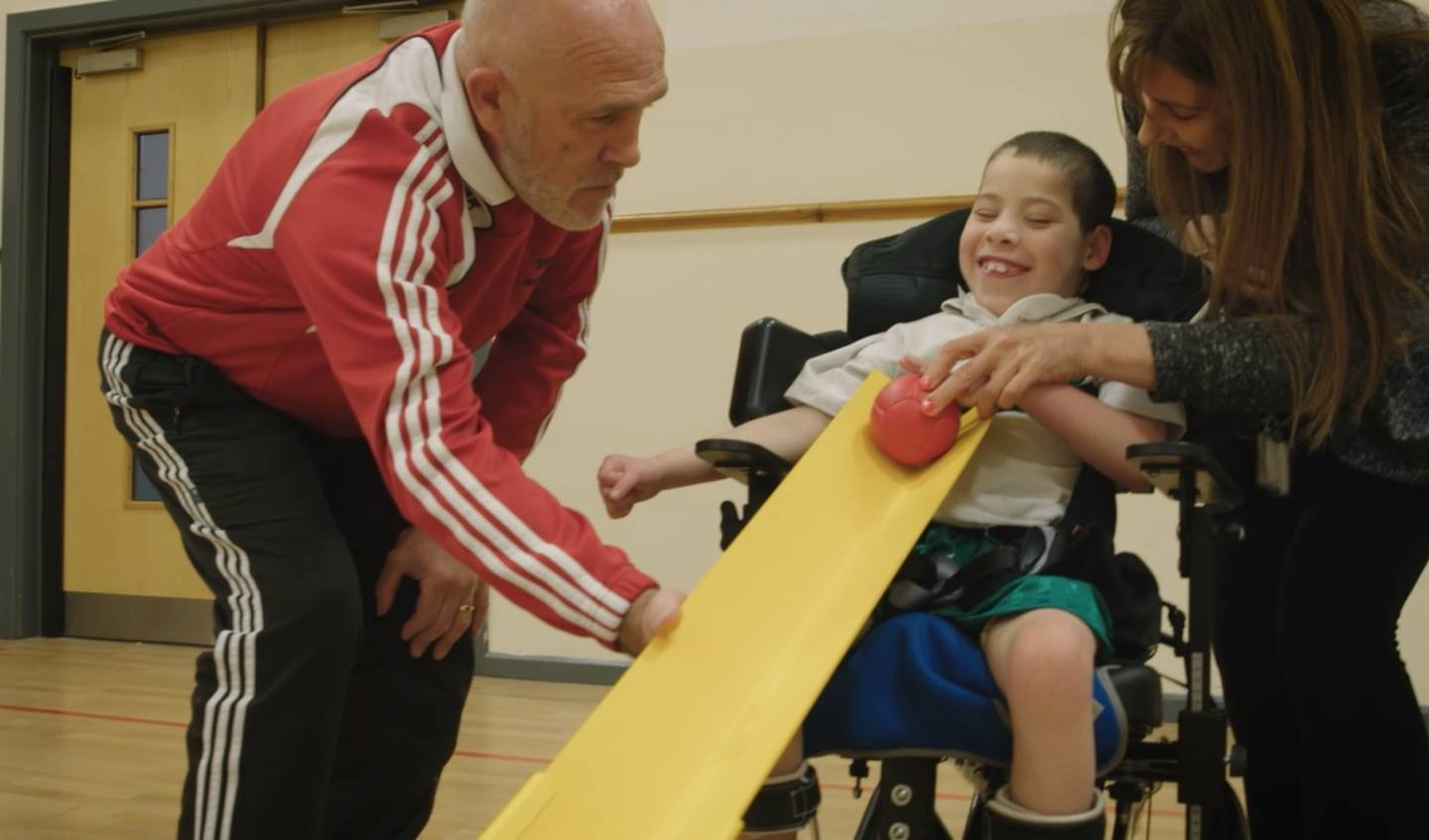 Young boy playing boccia with teacher and supporter