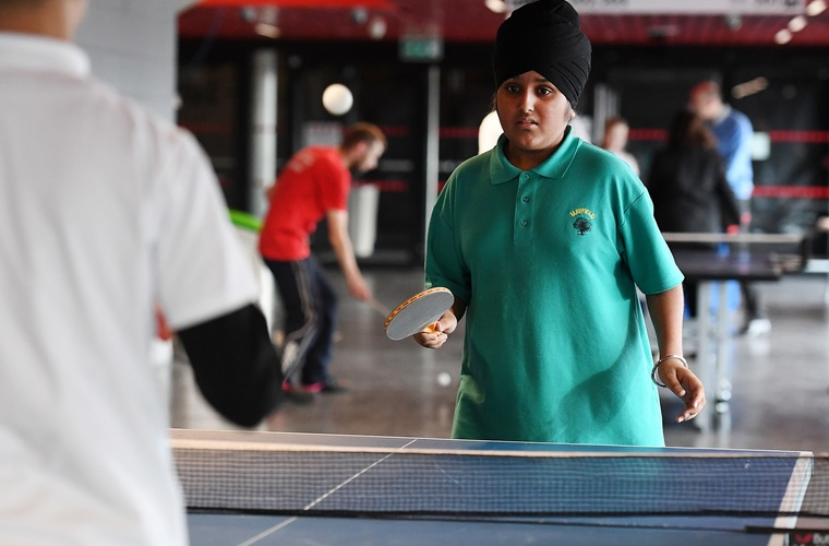Boy playing table tennis at school event