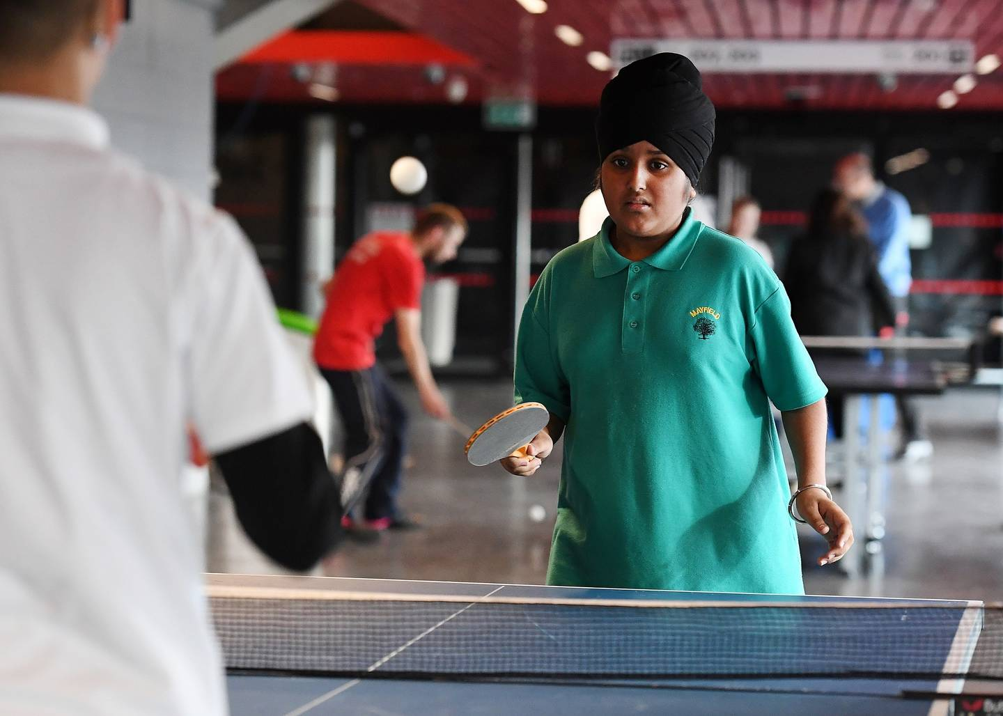 Boy plays table tennis at school event
