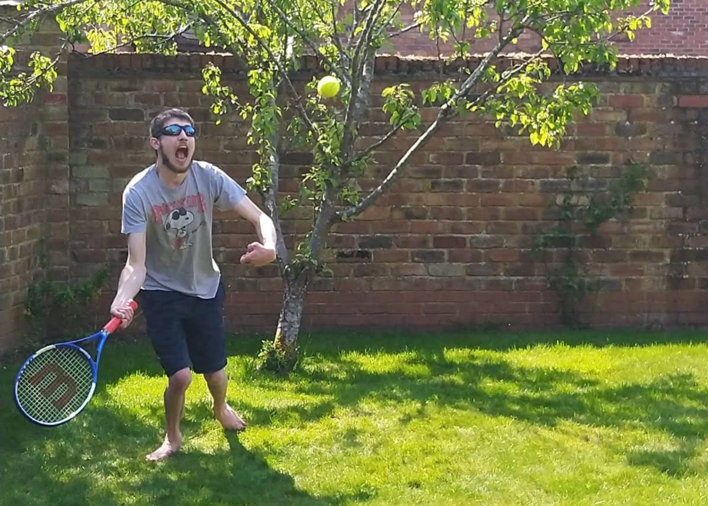 George playing tennis in garden