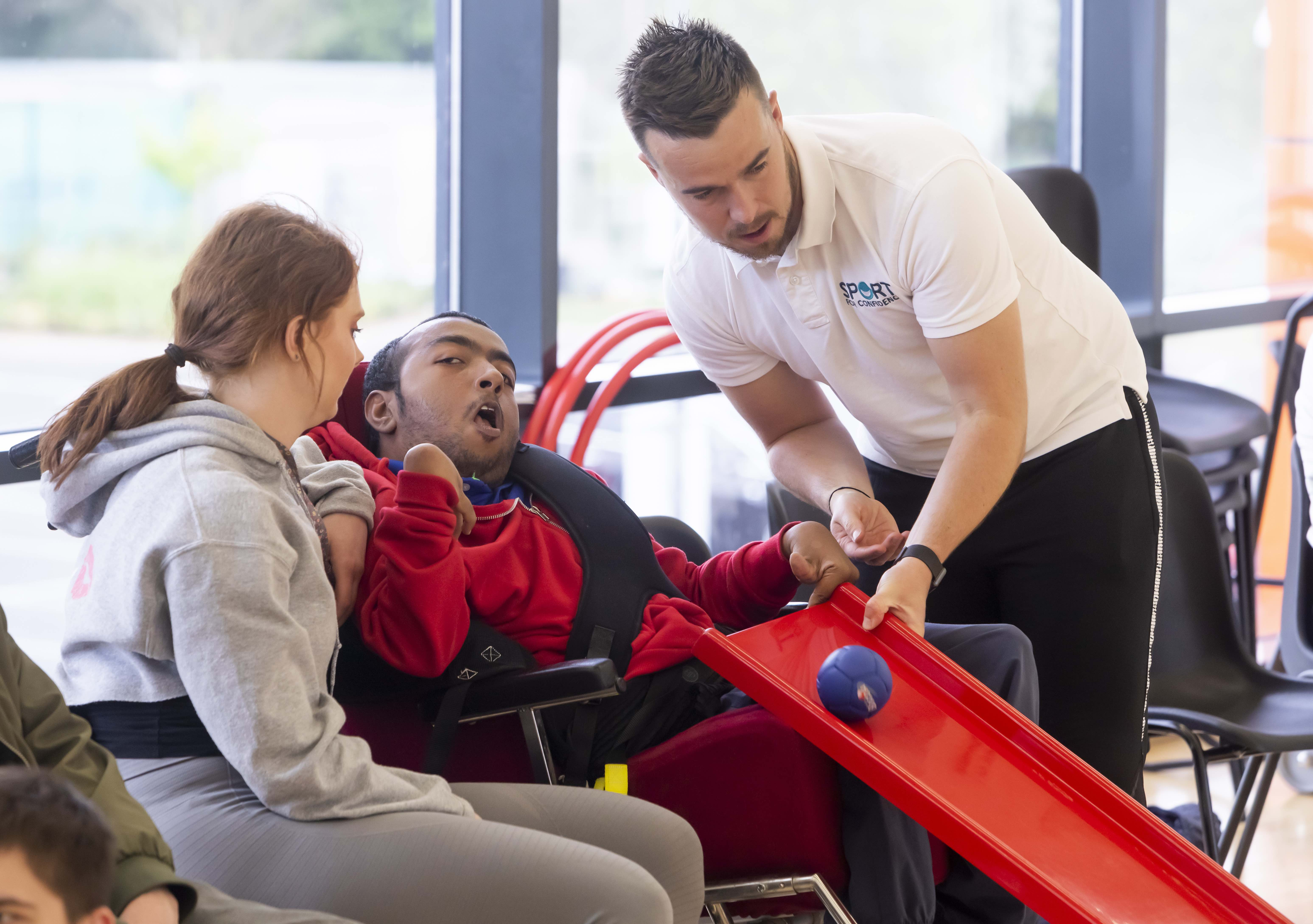Sport for Confidence client session shows occupational therapist supporting a disabled man with Boccia.
