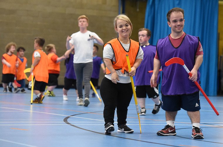 Two young adults with dwarfism playing indoor hockey