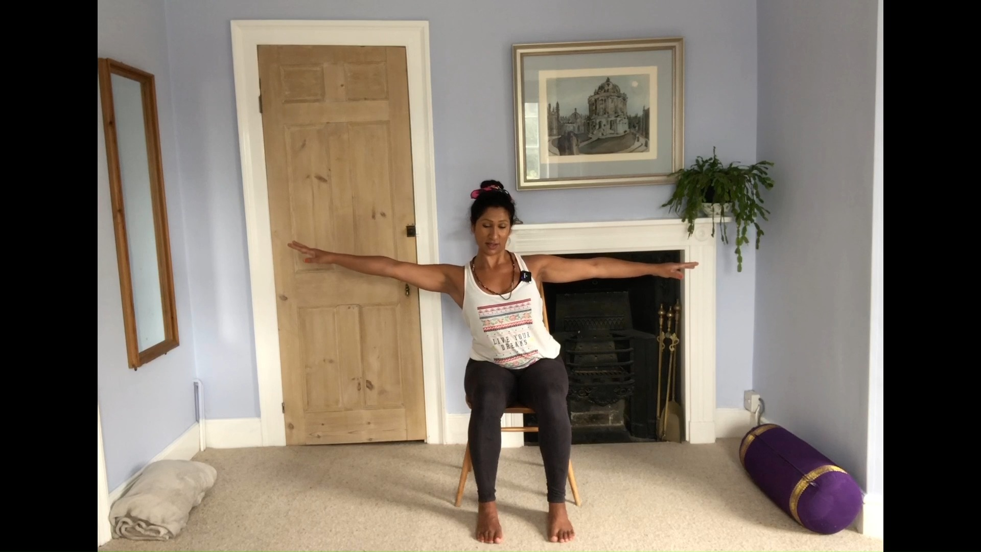 Basma Gale, Adaptive Yoga LIVE coach, doing a seated yoga exercise